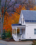 Front porch of New England home with autumn colors of sugar maples, Rochester, Vermont.