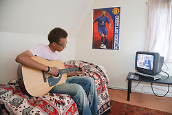 Young man in bedroom playing the guitar with the television on.