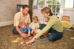 Couple sitting on living room floor playing with young daughter and son,