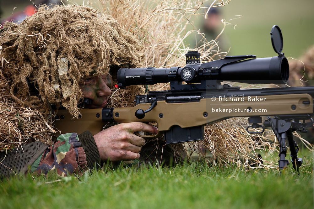 Lying on his stomach, a camouflaged British infantry soldier is seen looking down the telescopic sight of the new British-made Long Range L115A3 sniper rifle on Salisbury Plain, Warminster, England. Sniping means concealment, observation and assassination, a strategy the British are using more against the Taliban in Afghanistan. Swiss Lapua .338 inch rounds (8.59mm) travel at sub-sonic speeds of 936 metres/sec, finding its target accurately up to 1,100 metres. The rifle weighs 6.8kg with telescopic image-intensified scopes to 25x life size vision, made by Schmidt & Bender. Front-mounted 'suppressor' minimises the signature normally compromising snipers' position. At £23,000 each, a £4 million contract has been awarded to Accuracy International, to provide the Army, Royal Marines and RAF. The British say this is the best sniper rifle in the world.