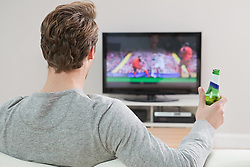 Dec. 04, 2012 - Young man watching football on television with beer bottle (Credit Image: © Image Source/ZUMAPRESS.com)