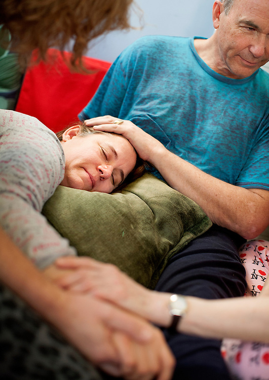 Diane Long releases some tears as she is held and supported during a Cuddle Party at a home in Minneapolis January 9, 2015. The feeling of Thomas Stout's hand on her head brought back some powerful personal memories, and the moment offered her a safe space in which to truly feel those emotions.