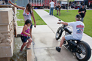 In an effort to beat the heat, Rebecca Konno of Las Vegas NM splashes water from the fountain on her friend eight-year-old Janessa Sigala (cq) during the Smoke out motorcycle rally Santa Rosa NM on Saturday, June 19, 2010.