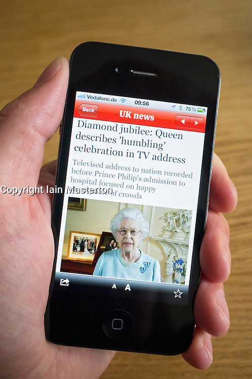 reading story about Queen's Diamond Jubilee using online newspaper App on an iPhone smartphone