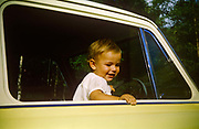 A young boy stands up in his father's Anglia car on a summer day out in the early nineteen sixties. Standing up on the driver's front seat the child smiles out of the open window while the car is parked on a day out to the countryside. This is the new age of car ownership when newfound wealth meant families could afford to buy a vehicle and travel elsewhere after the war years of 1950s austerity. The Ford Anglia is a British car designed and manufactured by Ford in the United Kingdom. The Ford Anglia name was applied to four models of car between 1939 and 1967. 1,594,486 Anglias were produced, The picture was recorded on Kodachrome (Kodak) film in about  1961.
