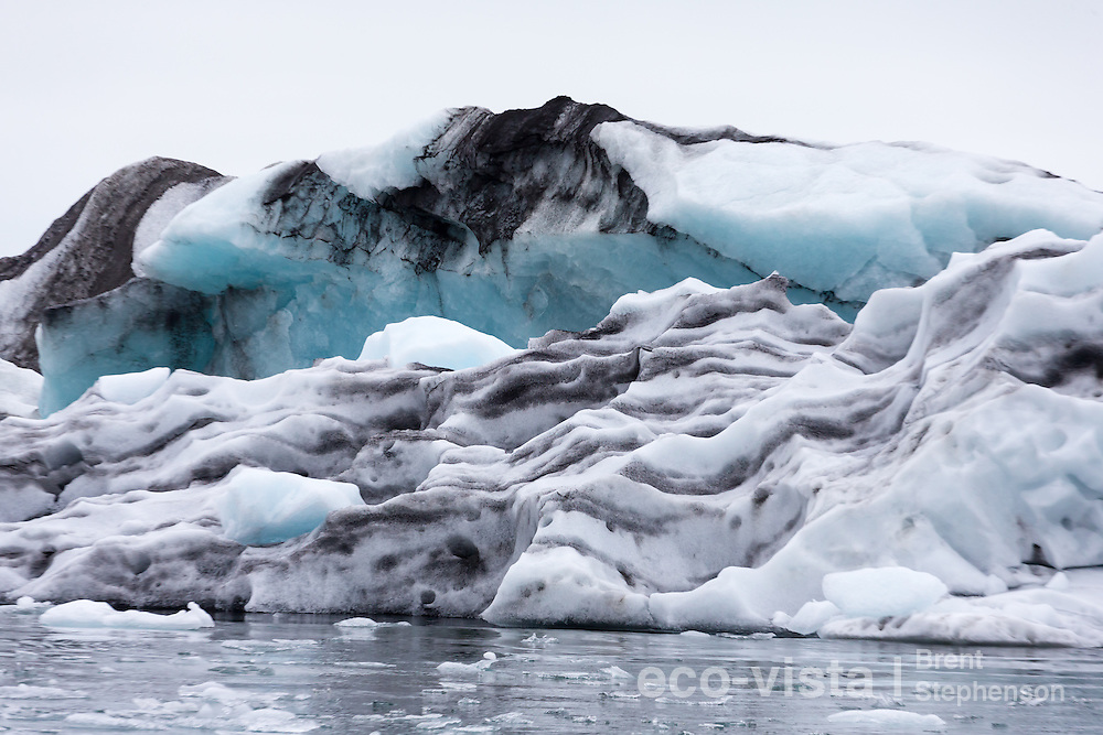 Glacial ice patterns and shapes, on a glacial lagoon. The volcanic dust from past eruptions, as well as rock and dirt from glacial action, give this ice its colour. Jokulsarlon, edge of Vatnajokull National Park, Iceland. July.
