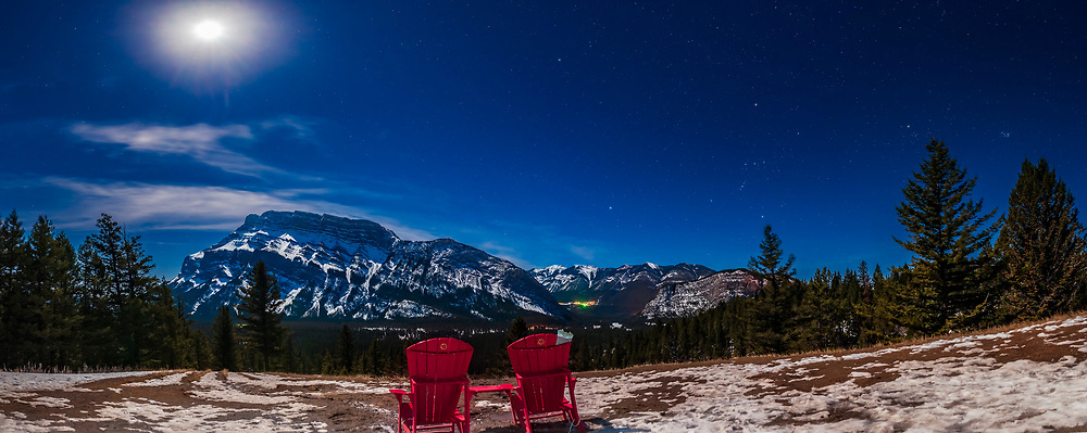 These are the iconic red chairs of Parks Canada, here on the Tunnel Mountain Drive viewpoint overlooking the Bow River and Mount Rundle, in Banff National Park, and under the moonlit winter sky, with Orion and Canis Major over the valley to the southwest. Sirius is the bright star over Sulphur Mountain to the right. <br /> <br /> This was March 18, 2019, with the scene illuminated by the gibbous Moon at top here. <br /> <br /> This is a panorama cropped from the original 12-segments, each 15 seconds at f/4 with the Sigma 24mm Art lens and Nikon D750 at ISO 800. Stitched with Adobe Camera Raw.  I added an Orton glow effect with Luminar 3. The chairs, being in shadow, I light painted briefly with a white LED light.