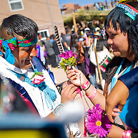 102712       Cable Hoover<br /> <br /> Julius Quetawki, left, ties a ribbon on the wrist of Brittney Kanteena as they prepare to dance in the Zuni Harvest Festival in Zuni Saturday.