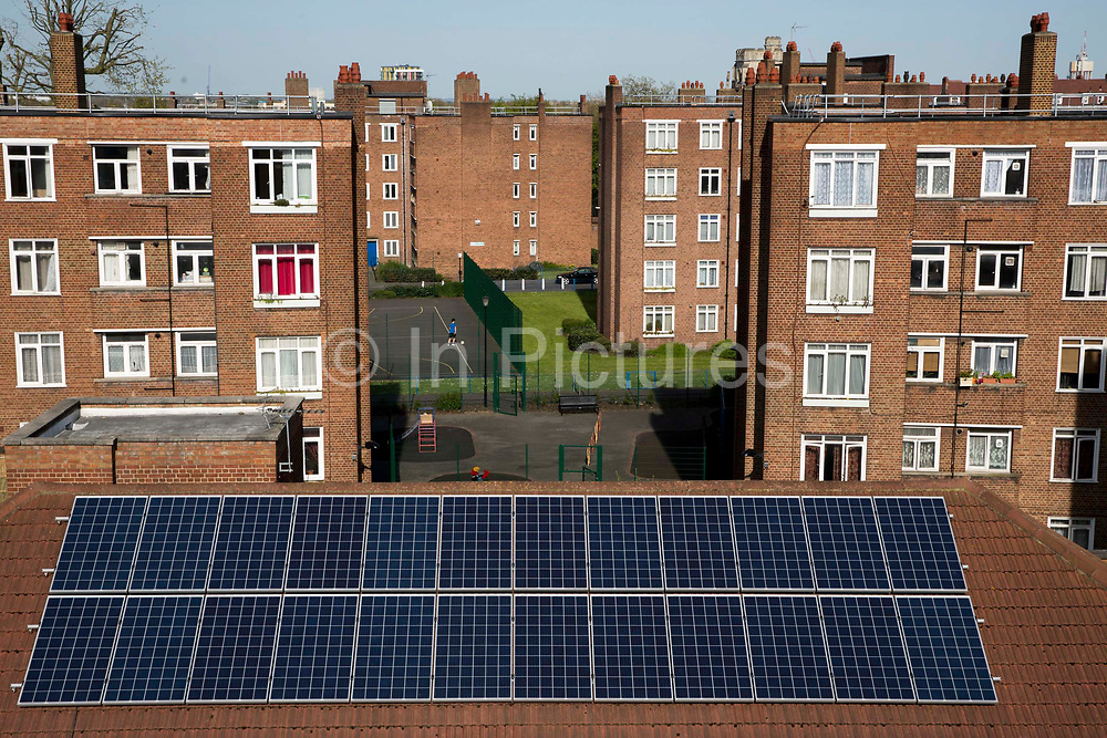Solar photo voltaic PV panels on the roof of Hackney council estate Bannister House, the first community solar installation on a estate in Hackney, London, United Kingdom. Bannister House was Hackney's first community solar installation, Banister House Solar, has been developed by Re-powering London in partnership with local estate residents and Hackney Council, and delivered using funds raised through a community share offer. The 102kWp solar array generates up to 82,000kWh of energy annually, saving 50,000kg of CO2 emissions. In addition, a portion of the revenue generated through the government's Feed-in Tariff and sale of energy over the 20-year life of the project will generate over £28,000 for the Banister House Solar community fund. Hackney, London.