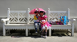 © Licensed to London News Pictures. 12/05/2012. Chiswick, UK.Brother and sister Amy and Daniel Wong hide under a pink umbrella in the sunshine.  People enjoy the sunshine in the grounds of Chiswick House today 12 Amy 2012. Photo credit : Stephen Simpson/LNP