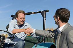 Farmer welcomes businessman with handshake while sitting on a tractor in cornfield, Bavaria, Germany
