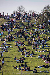 © Licensed to London News Pictures. 04/04/2021. London, UK. Members of the public relax in the sun on Easter Sunday at Primrose Hill, north London. Photo credit: Marcin Nowak/LNP