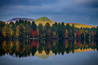 Dramatic storm clouds and early morning light during autumn on Ricker Pond in Groton State Forest, Vermont, USA