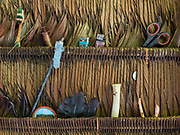 Various objects kept under the palm roof: lighter, flute made of bone, feathers, scissors, pods of beans, mirror, syringe, toothbrush.  House of Jose, 75, one of the oldest Tsimane.