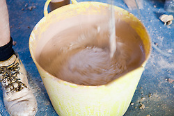 Using a mixing tool to stir plaster,