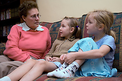 Grandmother and granddaughters sitting on the sofa,