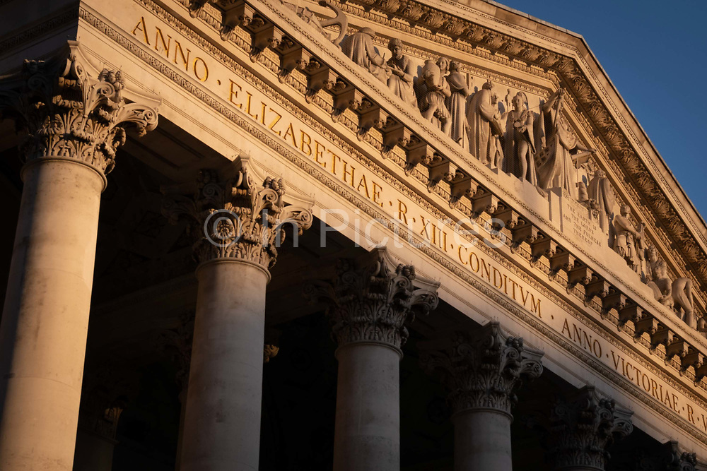 A sunlit detail of the friezes and Latin inscriptions on the pediment of the Royal Exchange in the City of London, the capitals financial district, on 27th February 2021, in London, England. At the top of Doric and Ionic columns with their ornate stonework, powerfully strong lintels cross, bearing the load of fine artistry and carvings which feature the design by Sir William Tite in 1842-1844 and opened in 1844 by Queen Victoria whose name is written in Latin Victoriae R. It's the third building of the kind erected on the same site. The first Exchange erected in 1564-70 by sir Thomas Gresham but was destroyed in the great fire of 1666. It's successor, by Jarman, was also burned down in 1838. The present building is grade 1 listed and cost about £150,000.