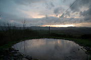 View at sunset over a plunge pool in the rain towards Machynlleth from Melinbyrhedyn in Wales, United Kingdom.