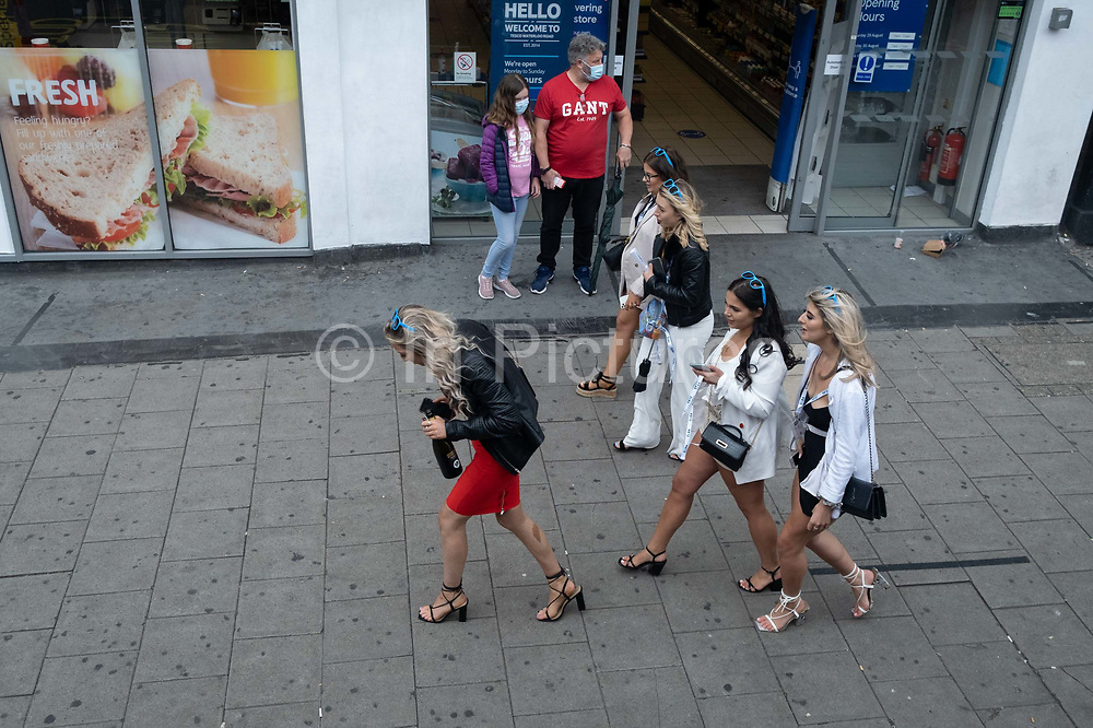 During the Coronavirus pandemic, when social distancing and partying is being discouraged, a group of hen party women walk through Waterloo, one of whom is swigging from a bottle of booze, on 29th August 2020, in London, England.