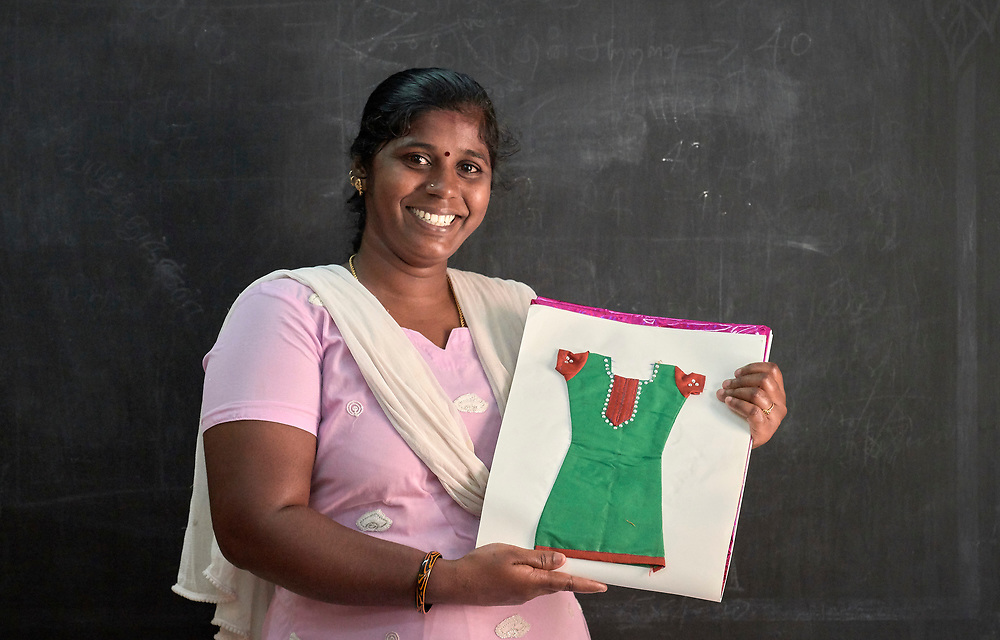 A participant in a sewing and tailoring class in Chennai, India, displays a sample of her work in the class. Taught by a Methodist deaconess, the class increases the women's earning capacity, providing money for family needs while at the same time gaining them respect in their homes and neighborhoods.