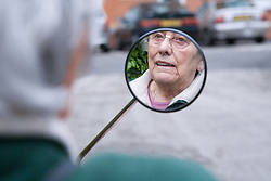 Reflection of older woman's face in wing mirror of an electric mobility scooter,