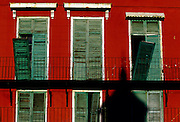 """The shadow of a church steeple is cast on green shutters on a red building in New Orleans, Lousiana. - To license this image, click on the shopping cart below - -- Determine pricing and license this image, simply by clicking """"Add To Cart"""" below --"""