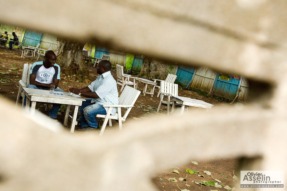 HIV/AIDS counselor Kevin Kouassi Gallet and Dr. Charles Joseph Diby sit in a bar  in Dimbokro, Cote d'Ivoire on Friday June 19, 2009.