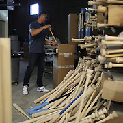 Pete Tucci, sorts through turned bats, the discards lay on the floor, in his factory, Tucci Lumber Company, which makes baseball bats. Norwalk, Connecticut, USA. 27th June 2014. Photo Tim Clayton