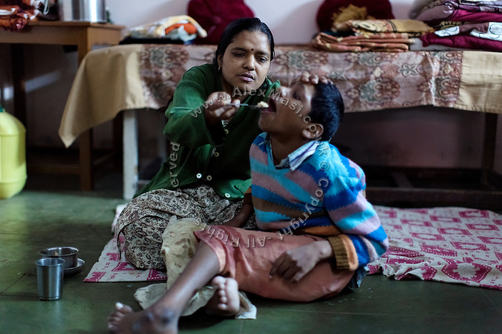 Siddhesh, 12, a boy suffering from severe celebral palsy is being fed lentils and soup by his mother, Meeta, 33, while inside their home in Nariyal Kheda, Bhopal, Madhya Pradesh, central India, site of the infamous 1984 gas tragedy. Siddhesh's father has abandoned him years ago. His mother is also suffering from mental retardation, and they now live with Siddhesh's maternal grandfather on the meagre pension he has earned after working as a civil servant. In 1984 Siddhesh's mother survived the poisonous gas cloud that enveloped Bhopal, leaving everlasting consequences that today continue to consume people's lives.
