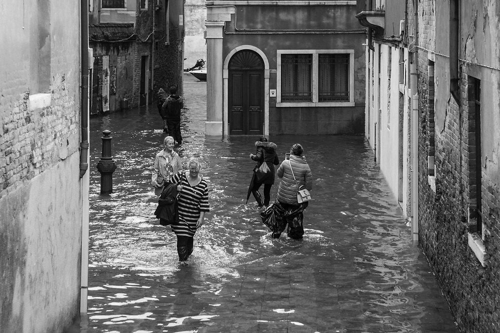 Venice, Italy. 29 October, 2018.  Citizens and tourists walk in a square covered by the high tide in Cannaregio district  on October 29, 2018, in Venice, Italy. This is a selection of pictures of different areas of Venice that the press has not covered, were resident live and every year they have to struggle with the high tide. Due to the exceptional level of the 'acqua alta' or 'High Tide' that reached 156 cm today, Venetian schools and hospitals were closed by the authorities, and citizens were advised against leaving their homes. This level of High Tide has been reached in 1979. © Simone Padovani / Awakening / Alamy Live News