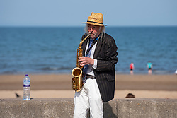 Portobello, Scotland, UK. 16 April 2021. Friday saw Covid-19 travel restrictions lifted meaning the public are free to travel around the country, Sunshine and warm temperatures saw Portobello beach and promenade busy on Saturday afternoon. Police patrols were evident but low key. Pic; A busker entertains the public. Iain Masterton/Alamy Live News