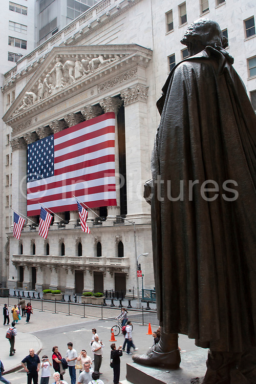 George Washington statue faces the  giant US flag outside the New York Stock Exchange on Wall Street on 20th May 2007 in New York City, United States.
