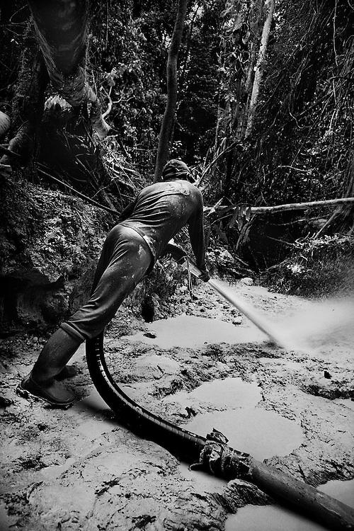 Guyane francaise, Yaou, concession miniere.<br /> <br /> Exploitation miniere clandestine sur la concession de la Societe Miniere Yaou Dorlin. <br /> A la suite de Guyanor en 1993, plusieurs societes investissent dans la prospection. L'or, une des rares exportations guyanaises, represente 264,9 MF en 1999 et emploie officiellement 900 personnes. Quelques multinationales gerent la majorite des sols, 200 km2 de titres sont attribues, on estime à 600 km2 la zone orpaillee clandestinement.<br /> Pompes et pelles mecaniques, les techniques et la main d'œuvre sont bresiliennes. La terre est retournee et lavee a la recherche de paillettes qui seront amalgamees par addition de mercure.