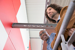 Two men meeting talking African Caucasian railing