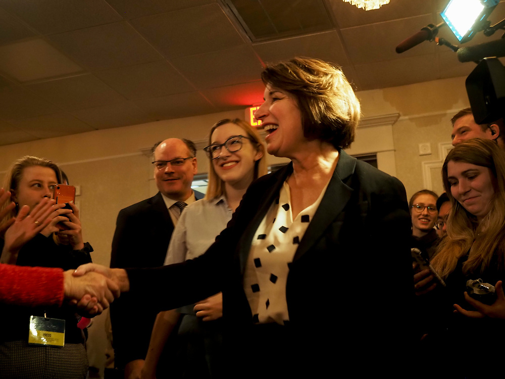 Amy Klobuchar greets supporters as her daughter, Abigail Klobuchar Bessler, and her husband John Bessler  look on at the Cedar Rapids Get Out the Caucus Rally
