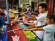 15 OCTOBER 2015 - BANGKOK, THAILAND: Children play with air guns at a shooting booth during the Vegetarian Festival at the Joe Sue Kung Shrine in the Talat Noi neighborhood of Bangkok. The Vegetarian Festival is celebrated throughout Thailand. It is the Thai version of the The Nine Emperor Gods Festival, a nine-day Taoist celebration beginning on the eve of 9th lunar month of the Chinese calendar. During a period of nine days, those who are participating in the festival dress all in white and abstain from eating meat, poultry, seafood, and dairy products. Vendors and proprietors of restaurants indicate that vegetarian food is for sale by putting a yellow flag out with Thai characters for meatless written on it in red.    PHOTO BY JACK KURTZ