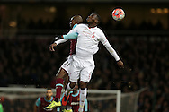 Christian Benteke of Liverpool and Angelo Ogbonna Obinze of West Ham United jump to head the ball. The Emirates FA cup, 4th round replay match, West Ham Utd v Liverpool at the Boleyn Ground, Upton Park  in London on Tuesday 9th February 2016.<br /> pic by John Patrick Fletcher, Andrew Orchard sports photography.