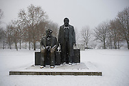 Snow falling on a statue of Karl Marx and Friedrich Engles in Alexander Platz near the route of the former Berlin Wall in the city centre. The route of the Wall, which stood from 1962-1989, has been developed into the 'Mauerweg,' a thoroughfare which traces most of the route of the Wall which encircled the city and divided it into East and West Berlin during the Cold War. In the years following the 1989 civil uprising in the German Democratic.Republic, most of the Wall was removed as part of the reunification strategy which united the pro-Soviet DDR and the Federal Republic of (West) Germany.