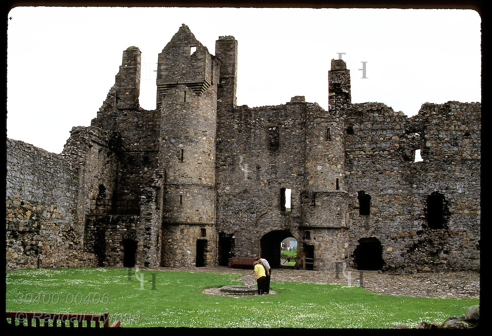 A couple stands in the interior courtyard of Balvenie Castle, built in 13th century; Dufftown. Scotland