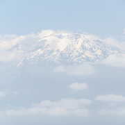The summit (Kibo Summit) of Mt Kilimanjaro seen from the distance below, with its snow and partly covered in clouds.