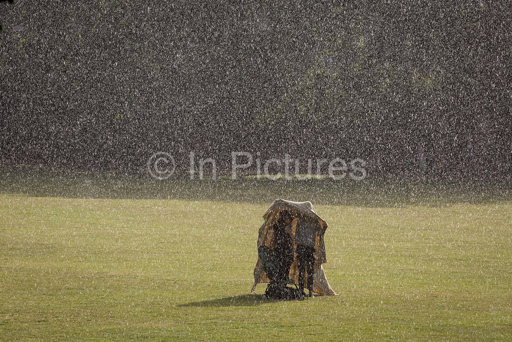 After an afternoon of sunshine and warm temperatures during the continuing UK Coronavirus lockdown, a couple with their child shelter under a picnic blanket after being caught by surprise by a sudden and torrential downpour of rain in Ruskin Park, a public green space in Lambeth, on 14th June 2020, in London, England. The current UK Covid-19 death toll now stands at 41,662, an increase over the last 24 hours of 181, although Prime Minister Boris Johnson is coming under pressure to review the case for a reduction of the 2 metre social distance rule, due to its effect on jobs and wider economy.