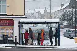 © Licensed to London News Pictures. 13/02/2013. Sheffield, Uk. People wait at a bus stop in Woodseats, Sheffield in freezing thick snow. There is more snow throughout Sheffield again today. Photo credit : David Mirzoeff/LNP