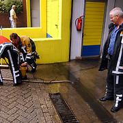 Wateroverlast na wolkbreuk Bibi's garage Eemlandweg  Huizen, werkvloer onder water, brandweer aan het pompen