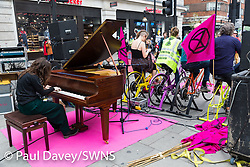 A woman plays a grand piano on Oxford Street whilst people use pedal power to supply electricity for the sound system as hundreds of environmental protesters from Extinction Rebellion occupy Marble Arch, camping in the square and even on the streets, blocking access to traffic on Park Lane and Oxford Street in London's usually traffic-heavy west end. . London, April 16 2019.