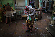 Hindu man walking in the rain in an alley in Varanasi Old town, in India.