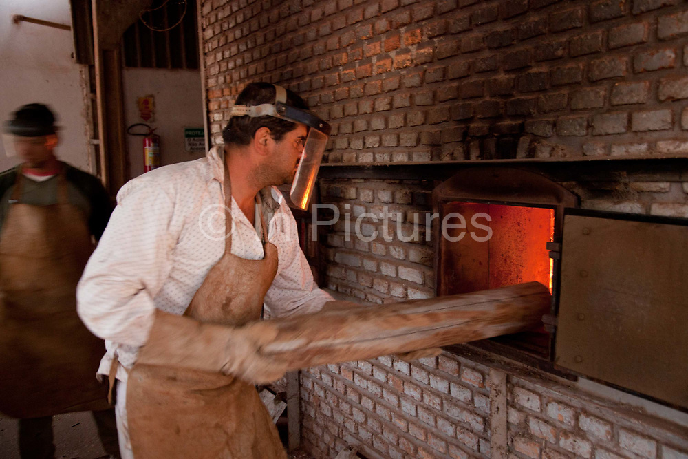 Young Brazilian man stoking a fire used to dry grain on a large soya and maize farm. Brazil is the largest producer of Sugar and Beef, then second for Soya and third for Maize. Many of the farms are in the state of Mato Grosso and Mato Grosso do Sul, they are often enournmous, stretching for miles kilometres. A lot of the crops are processed on site and kept in large warehouses or silos.