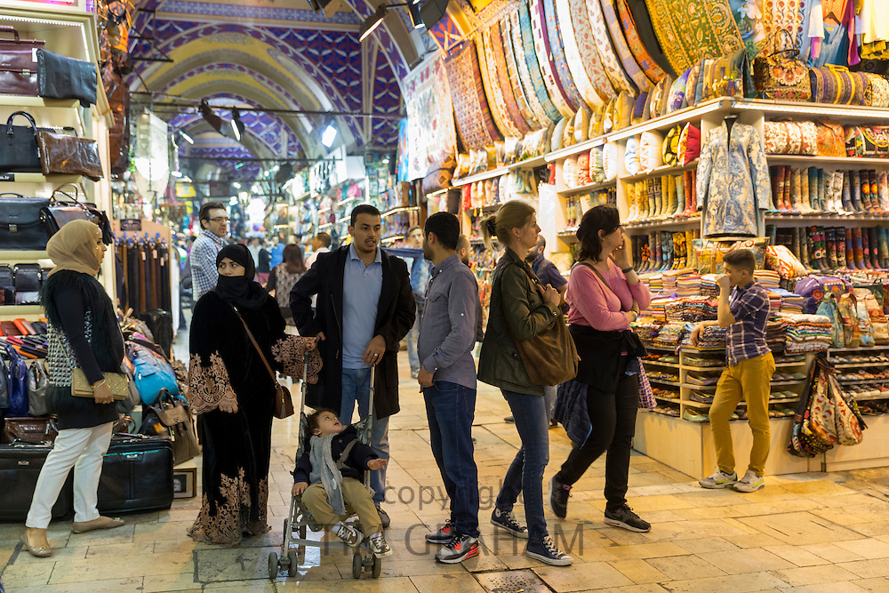 Muslim family shopping and tourists in The Grand Bazaar, Kapalicarsi, great market in Beyazi, Istanbul, Turkey