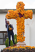 A Mexican woman places marigolds on a cross for the Day of the Dead festival in Santa Clara del Cobre, Michoacan, Mexico.