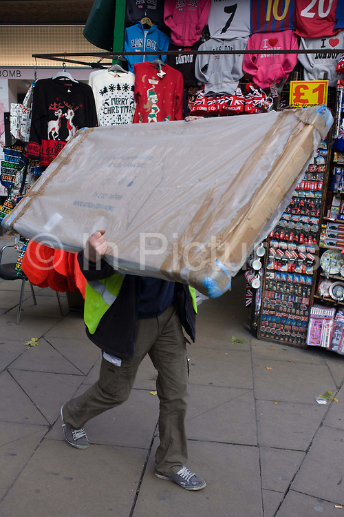 Workman carries awkward construction panel through a London street. Hidden by the large panel that he manhandles on his shoulder, the man walks past a stall selling tourist trinkets in the West End of London. He delivers the load to a nearby site.
