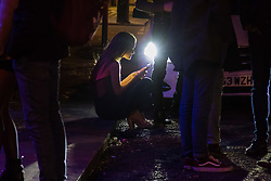 London, January 01 2018. A woman sits on the pavement using her phone on Frith Street as revellers in London's West End enjoy New Year's Eve. © SWNS